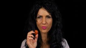 Femme joyeuse à un régime de vegan mangeant des tomates-cerises un concept de la nutrition saine banque de vidéos