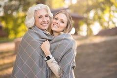 Femme joyeuse étreignant la mère retirée au pique-nique Photographie stock libre de droits