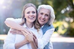 Femme joyeuse appréciant la promenade avec la mère pluse âgé sur la rue Images stock