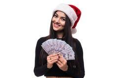Femme joyeuse de brune dans la robe rouge lui montrant l'argent liquide sur le fond blanc Photographie stock