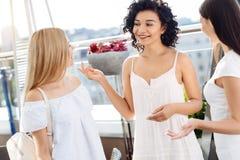 Femme joyeuse de brune parlant avec ses amis Image stock