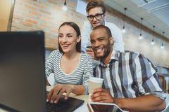 Femme joyeuse et hommes détendant en café d'Internet Photo stock