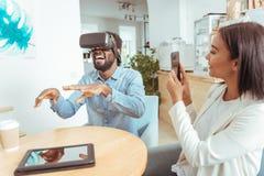 Femme joyeuse filmant son casque de l'essai VR d'ami Images libres de droits