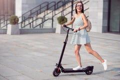 Femme joyeuse montant un scooter de coup-de-pied photos libres de droits
