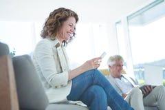 Femme joyeuse par l'homme à l'aide du comprimé numérique Photo stock