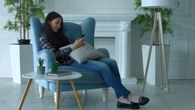 Femme joyeuse passant en revue le media social au téléphone portable banque de vidéos