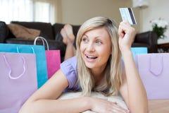 Femme joyeuse retenant un par la carte de crédit après l'achat Photographie stock libre de droits