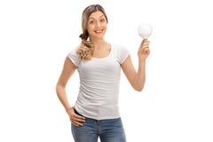 Femme joyeuse tenant une ampoule de LED image stock