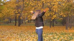 Femme joyeuse tournant autour dans les feuilles d'Autumn Park Holding Golden Yellow banque de vidéos