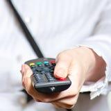 Femme jugeant à télécommande et poussant le bouton de puissance Photos stock