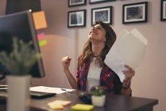Femme jugeant des documents joyeux après une réussite commerciale photos stock