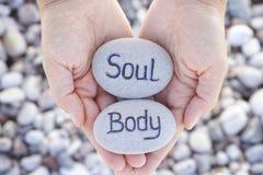 Femme jugeant en pierre avec l'âme et le corps de mots dans des ses paumes Photo stock