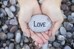 Femme jugeant en pierre avec l'amour de mot dans des ses paumes Photographie stock libre de droits