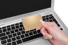 Femme jugeant la carte de crédit d'or disponible Image stock