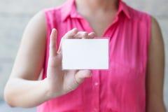 Femme jugeant la carte de crédit en blanc disponible Images stock