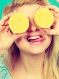 Femme jugeant le citron de fruit demi sur des yeux Image stock