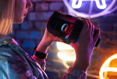Femme jugeant le dispositif en verre de casque de vr illuminé avec la lampe au néon futuriste photo stock