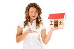 Femme jugeant le modèle de la maison d'isolement sur le fond blanc Photographie stock libre de droits
