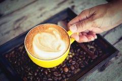 Femme jugeant le moka de café chaud sur la table en bois Photo libre de droits
