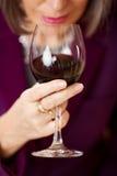 Femme jugeant le vin rouge en verre Images libres de droits