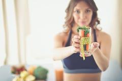 Femme jugeant un verre à boire plein de la salade de fruit frais avec un ruban métrique autour du verre photographie stock libre de droits