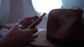 femme 4k asiatique tenant le smartphone avec des mains pendant le vol banque de vidéos