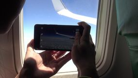 femme 4K asiatique utilisant le téléphone intelligent par la fenêtre un avion banque de vidéos
