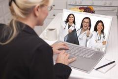 Femme à l'aide de l'ordinateur portable regardant trois médecins avec des pouces  Photo libre de droits