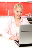 Femme à l'aide de l'ordinateur portatif dans la cuisine Photos libres de droits