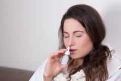 Femme à l'aide de la pulvérisation nasale dans son salon Photo stock