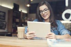 Femme à l'aide du comprimé en café Image stock