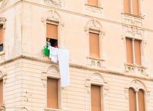 Femme la fenêtre de son vieil immeuble accrochant sa blanchisserie pour sécher photo stock