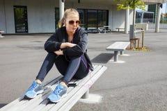 Femme à la mode dans les vêtements de sport écoutant la musique sur le banc Photos libres de droits