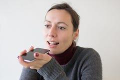 Femme laissant un massage de voix au téléphone photographie stock libre de droits