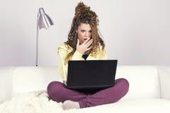 Femme latine étonnée travaillant avec son ordinateur portable sale Photographie stock
