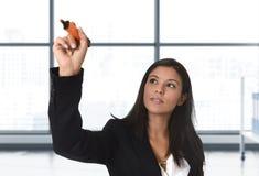 Femme latine d'affaires dans l'écriture formelle de costume avec le marqueur sur l'écran virtuel invisible ou conseil au bureau m Photos stock