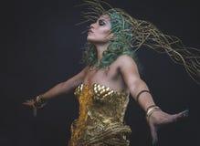 Femme latine de relaxation avec le costume vert de cheveux et d'or avec Han Photos libres de droits