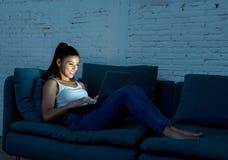 Femme latine heureuse travaillant tard la nuit sur son ordinateur portable image stock