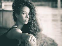 Femme latine regardant l'appareil-photo tout en touchant son monochrome de cheveux Photo libre de droits