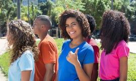 Femme latine riante avec le groupe de jeunes adultes montrant le pouce Photos stock