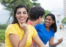 Femme latine riante dans une chemise jaune avec des amis Photographie stock