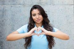 Femme latino-américaine de sourire dans l'amour montrant le coeur avec des mains photographie stock
