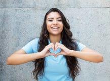 Femme latino-américaine riante dans l'amour montrant le coeur avec des mains photo stock