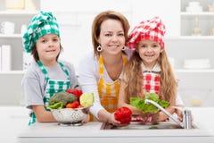Femme lavant les légumes avec les enfants photographie stock libre de droits