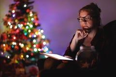 Femme le réveillon de Noël, utilisant le comprimé images libres de droits