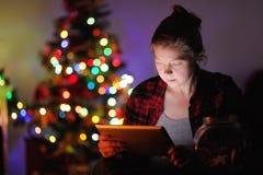 Femme le réveillon de Noël, utilisant le comprimé photo libre de droits