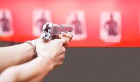 Femme les deux mains tenant l'arme à feu de magnum, index sur le déclencheur, viser prêt à tirer sur des cibles sur le fond rouge photos libres de droits