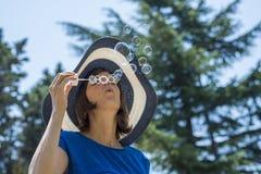Femme élégante dans les bulles de soufflement d'un chapeau de soleil de paille Image libre de droits