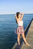 Femme libre appréciant l'été avec les bras ouverts sur la plage Images stock