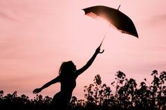 Femme libre débranchée de silhouette avec la mouche de parapluie à l'avenir Photo stock
